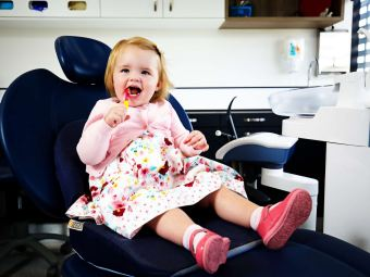 Child on dental chair brushing her teeth